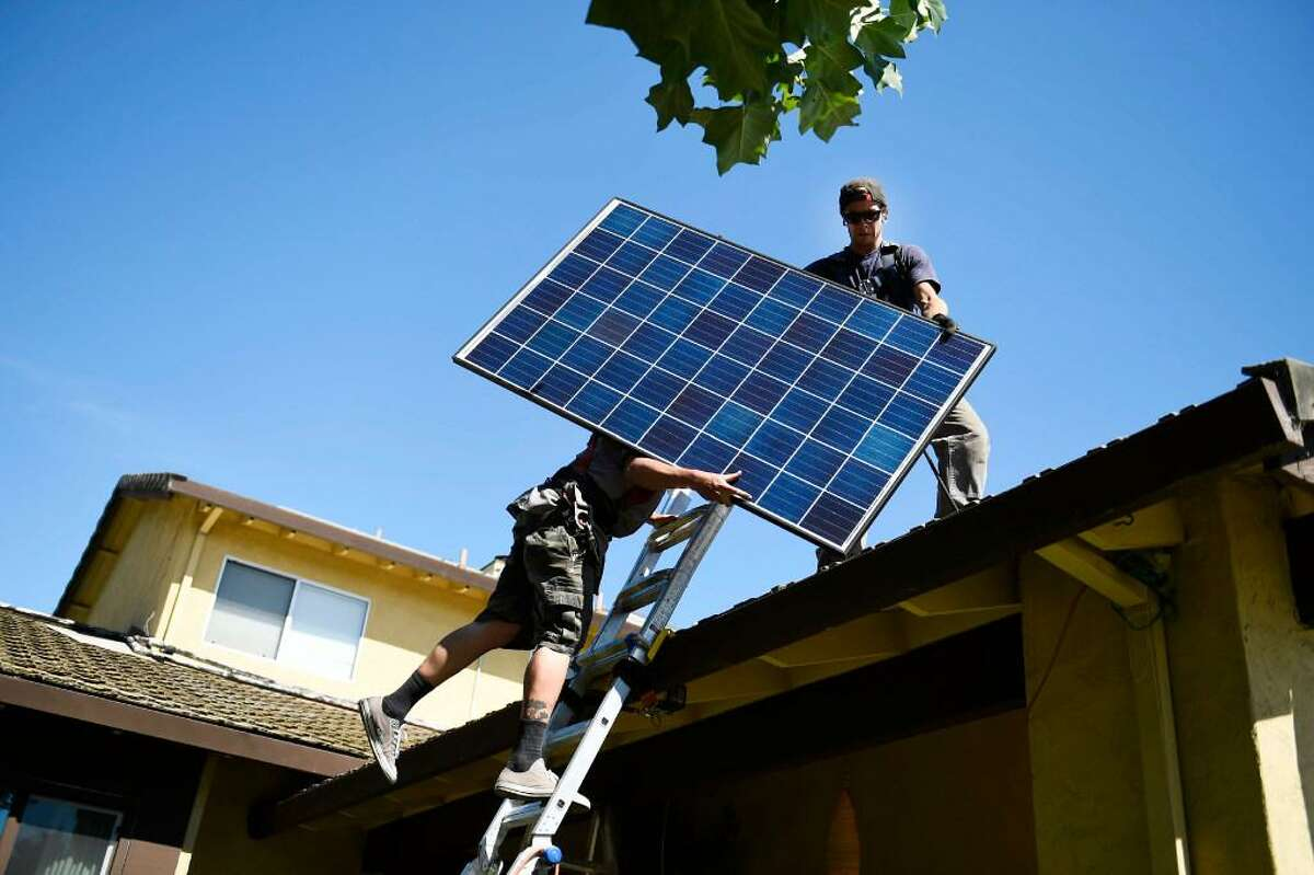 SunRun installers Brandon Anderson and Will LaRocque install one of 28 Q-Cell panels on a Sunnyvale home in 2016.