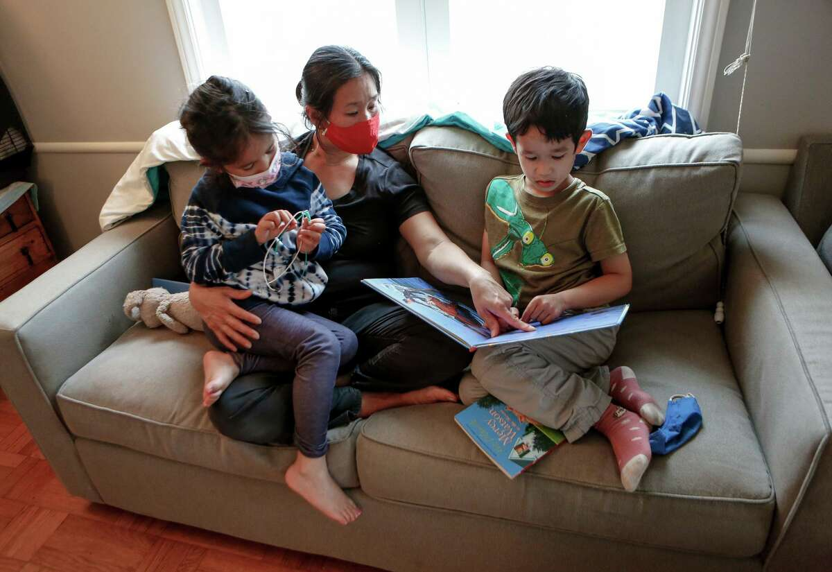 Kimberly Shu reads with her 7-year-old twins, Zoe (left) and Lucas, in their San Francisco home. Shu is a low-income single mom and doesn't know what her children will do until she's off work at the end of the day.