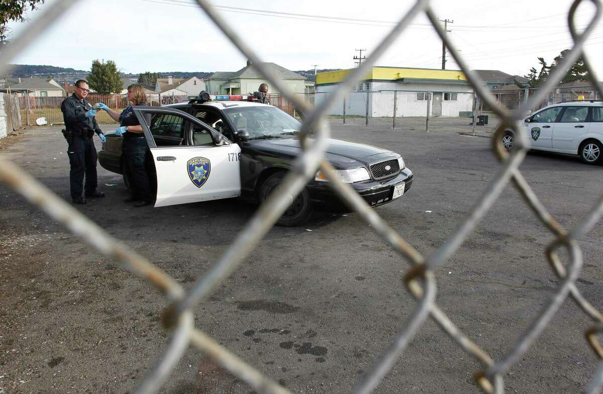 This file photograph shows Oakland police officers gathering evidence on Saturday December 31, 2011, where a 5-year-old boy was shot and killed near the corner of 55th Ave. and International Blvd. in Oakland.