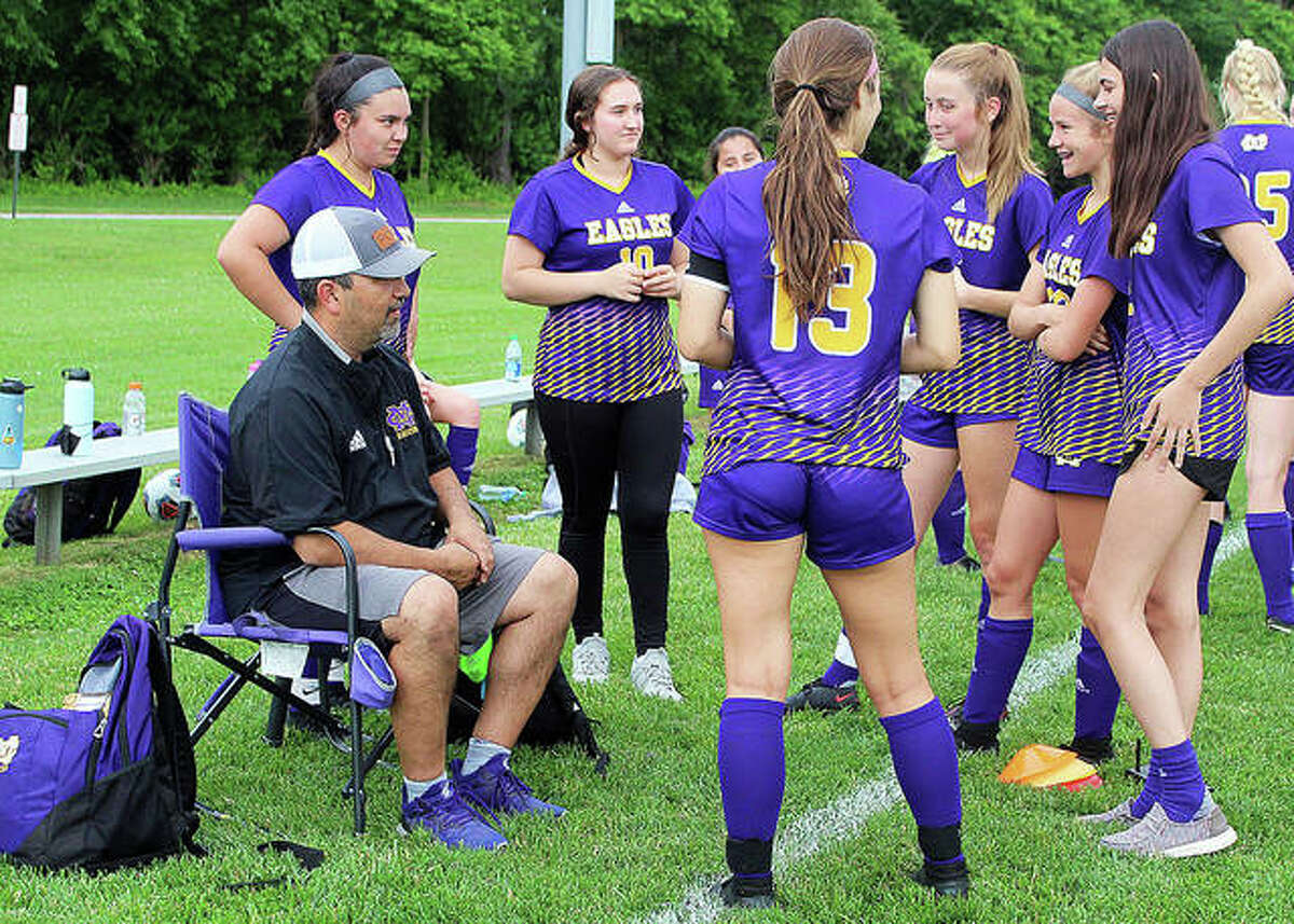 Civic Memorial coach Eric Zyung talks with his team after giving halftime instructions during CM's 7-0 playoff victory over Charleston at the Bethalto Sports Complex.