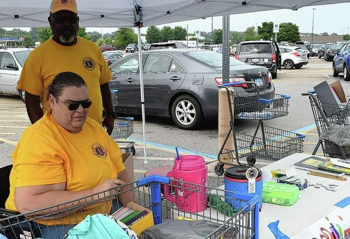 Lions Club members Sue Bower and Aaron Singleton collect school supplies Friday during the Stuff the Bus event at Walmart at 1941 W. Morton Ave. Money and supplies will be collected from 9 a.m. to 4 p.m. today and Aug. 6-7. The supplies will be distributed to Jacksonville School District 117 students.