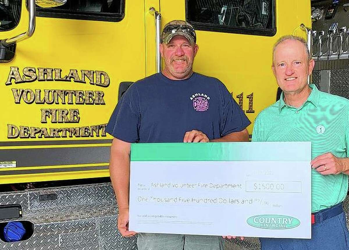 """Country Financial representative Rick Pettit (right) presents a check representing a $1,500 Operation Helping Heroes donation to Tyler Lathom, chief of Ashland Volunteer Fire Department. The money will be used to help the department buy emergency-extraction equipment. """"First responders are invaluable to the protection of our communities, and it's vital that these brave men and women are equipped with the tools necessary for their jobs,"""" Pettit said. Country Financial donated $3 million in 2020 to organizations and programs that support first responders and active-duty service members, supporting the company's vision to """"enrich lives in the communities we serve."""""""
