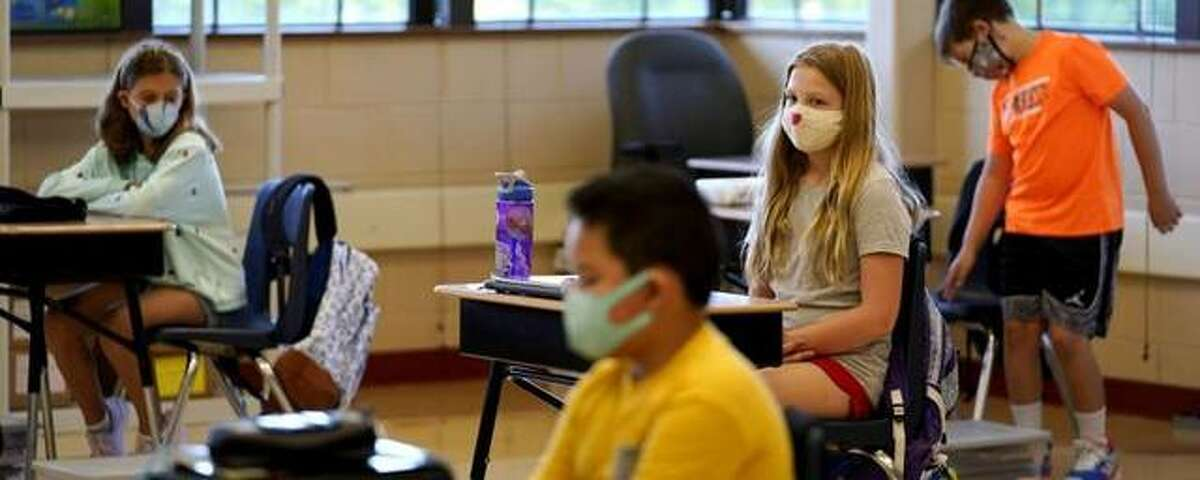 Fifth-graders wear masks as they wait for their teacher in the classroom.