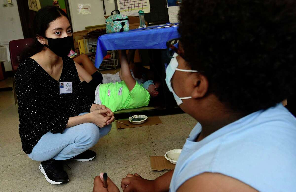Intern Andrea Bartes talks with a student during the ASPIRE summer program at the Familty and Children's Agency facility at Franklin School Tuesday, July 20, 2021, in Norwalk, Conn.