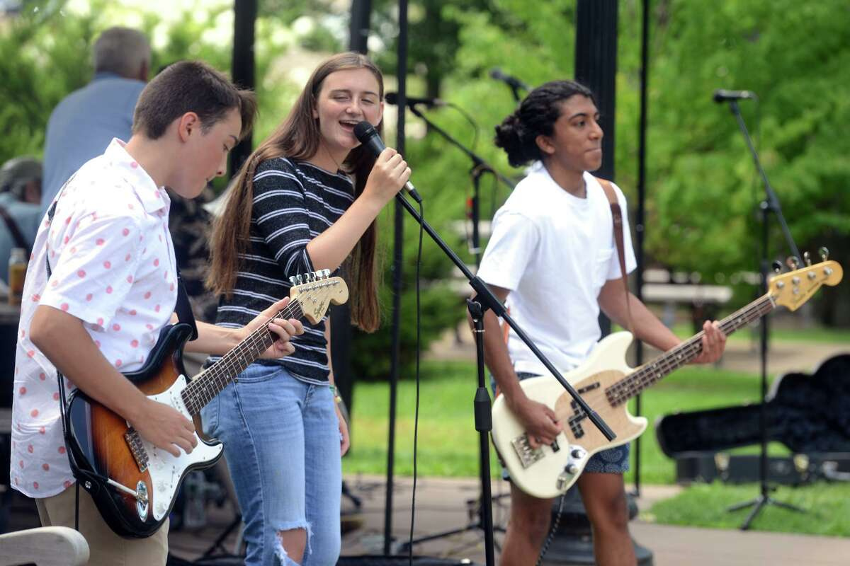 Members of the Perfect Fifth, from left, Jack Iozzo, Molly Kriskey and Rohan Subramaniam play during the weekly Free Music Fridays concert at Greenwich Common, in Greenwich, Conn. July 30, 2021. Produced by Greenwich Forward, Re-Imagine Greenwich, and the Town of Greenwich Parks and Recreation, Free Music Fridays will feature different performers every week at 12:30 through Sept. 3.