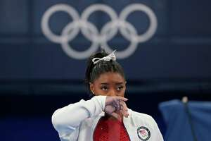 Simone Biles, of the United States, watches gymnasts perform after an apparent injury, at the 2020 Summer Olympics, Tuesday, July 27, 2021, in Tokyo. Biles withdrew from the team finals.