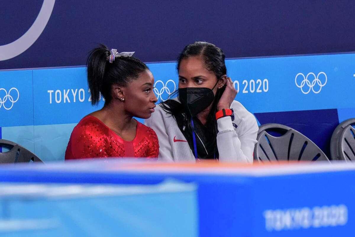 Simone Biles talks to a U.S. trainer during the women's gymnastics team final.