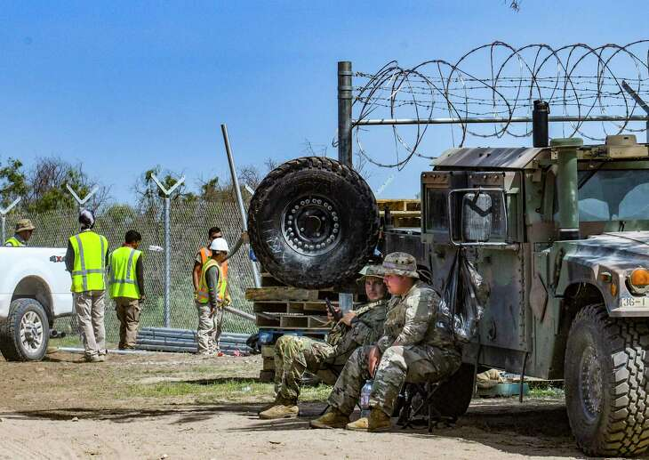 Members of the Texas National Guard take shelter from the heat by their vehicle as a crew installs new fencing on the border near Del Rio on Wednesday. Gov. Greg Abbott has escalated the role of the guard and Department of Public Safety in an effort to stop the migration.