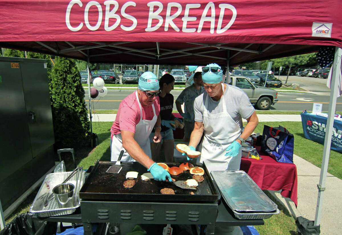 John Rawlinson, left, and Gary Cunningham serve up hot dogs and hamburgers during COBS Bread store's BBQ fundraiser for Swim Across America Fairfield County in Greenwich, Conn., on Saturday July 31, 2021. They are also holding one on Sunday at their store at 1057 High Ridge Road, Stamford. And, both stores will also donate $1 of every sale of gourmet hamburger and hot dog buns through Aug. 8 to the group