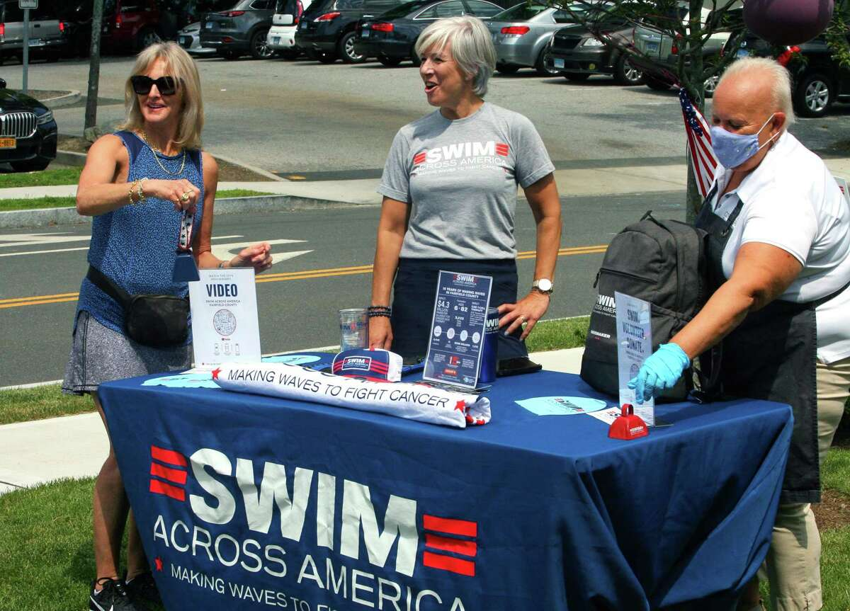 Jane Rawlinson, left, Nancy Carr, co-chair of Swim Across America of Fairfield County, and Louise Hyden, co-owner of COBS Bread store, hang out together at a BBQ fundraiser for Swim Across America Fairfield County at the store in Greenwich, Conn., on Saturday July 31, 2021. They are also holding one on Sunday at their store at 1057 High Ridge Road, Stamford. And, both stores will also donate $1 of every sale of gourmet hamburger and hot dog buns through Aug. 8 to the group.