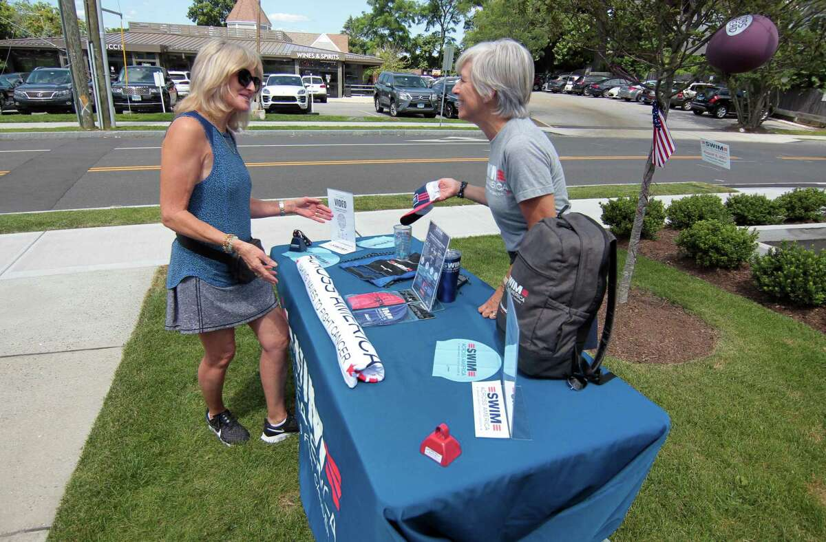 Jane Rawlinson, left, chats with Nancy Carr, co-chair of Swim Across America of Fairfield County, during COBS Bread store's BBQ fundraiser for Swim Across America Fairfield County in Greenwich, Conn., on Saturday July 31, 2021. They are also holding one on Sunday at their store at 1057 High Ridge Road, Stamford. And, both stores will also donate $1 of every sale of gourmet hamburger and hot dog buns through Aug. 8 to the group.