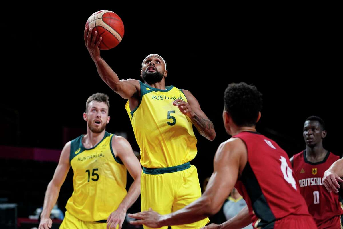 Australia's Patty Mills (5) drives to the basket over Germany's Maodo Lo (4) during a men's basketball preliminary round game at the 2020 Summer Olympics, Saturday, July 31, 2021, in Saitama, Japan. (AP Photo/Charlie Neibergall)