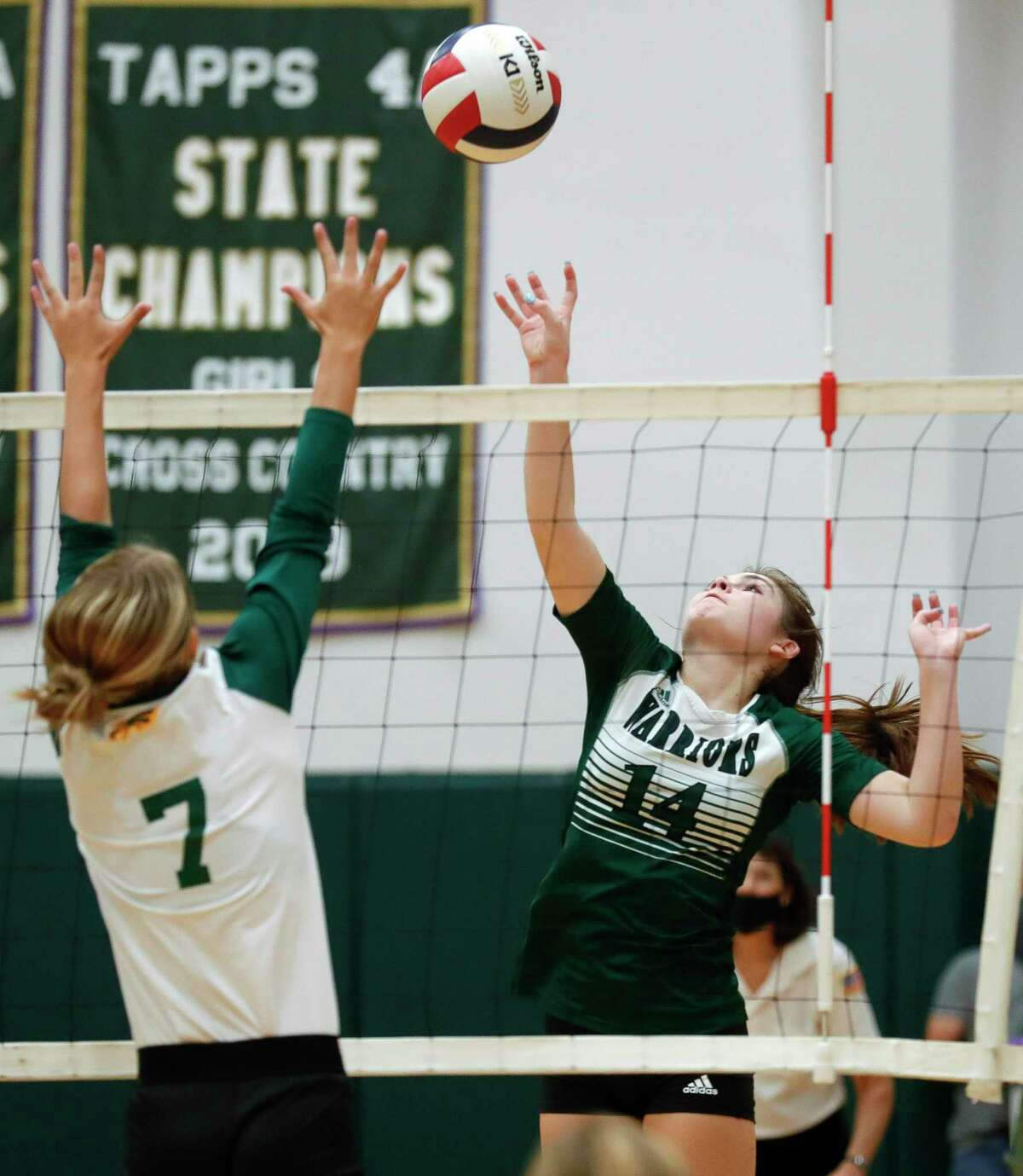 The Woodlands Christian Academy outside hitter Jordan Booth (14) tips the ball over Fort Bend Christian Academy setter Reagan Heflin (7) during the second set of a TAPPS high school volleyball match at The Woodlands Christian Academy, Tuesday, Sept. 29, 2020, in The Woodlands.