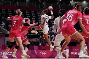 France's Estelle Nze Minko, center, tries to score during the women's Preliminary Round Group B handball match between the Russian Olympic Committee and France at the 2020 Summer Olympics, Saturday, July 31, 2021, in Tokyo, Japan. (AP Photo/Pavel Golovkin)