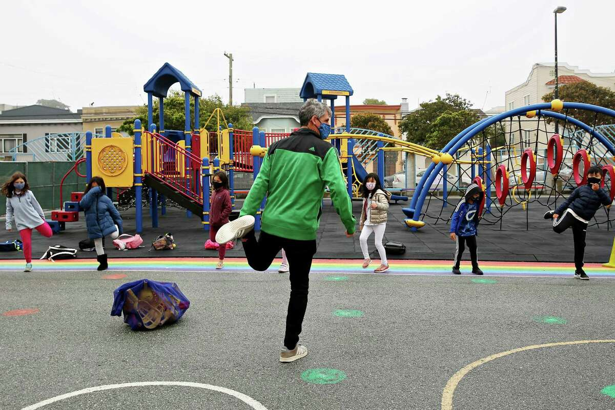 Third-grade teacher Jacob Strohm leads an exercise in the schoolyard on the first day Argonne Elementary in San Francisco is back in class.