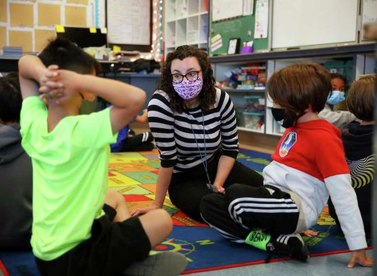 Fourth-grade teacher Erin Flathers talks with students as they work in pairs during a morning class exercise at Argonne Elementary School.