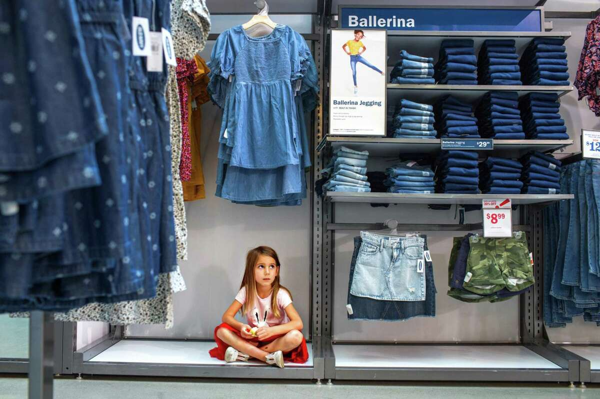 Luseni, 4, sits and waits for her sister to try on clothes on a back-to-school shopping trip at Old Navy, accompanied by her mother, Vaneni Vardanyan.