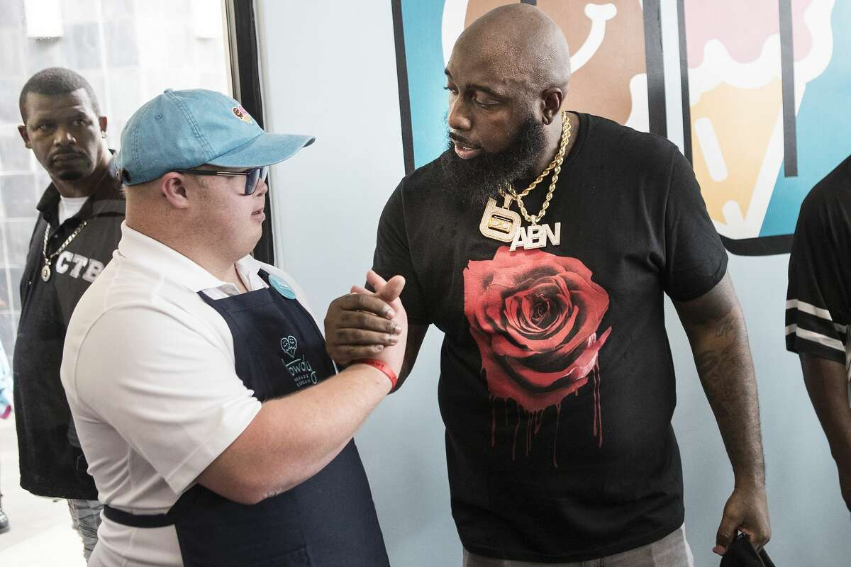 Trey Brandt, left, shakes hands with Trae the Truth during the grand opening of Howdy Homemade Ice Cream Thursday, July 22, 2021 in Katy. Hundreds of people flocked to the new ice cream franchise, owned and run by Houston rap artist, activist and philanthropist Trae tha Truth and his business partner Roderick Batson. The shop's mission is not just to serve up hand scooped ice cream but to also give employment opportunities to adults with special needs.