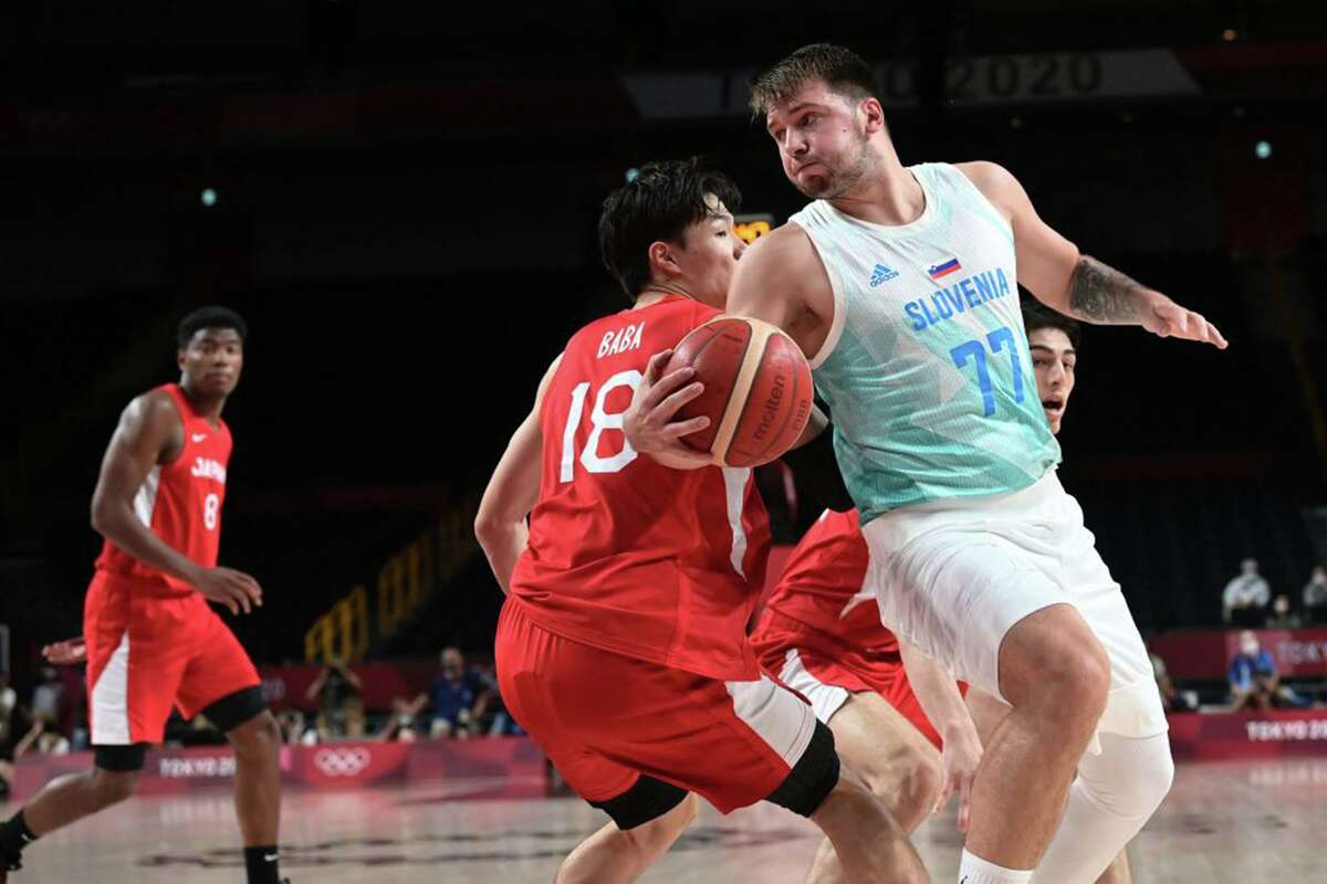 Slovenia's Luka Doncic dribbles past Japan's Yudai Baba (left) in the men's preliminary round group C basketball match between Slovenia and Japan during the Tokyo 2020 Olympic Games at the Saitama Super Arena in Saitama on July 29, 2021. (Aris Messinis/AFP via Getty Images/TNS)