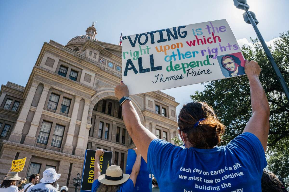AUSTIN, TEXAS - JULY 31: People display signs during the Georgetown to Austin March for Democracy rally on July 31, 2021 in Austin, Texas. Texas activists and demonstrators rallied at the Texas state Capitol after completing a 27-mile long march, from Georgetown to Austin, demanding federal action on voting rights legislation. (Photo by Brandon Bell/Getty Images)