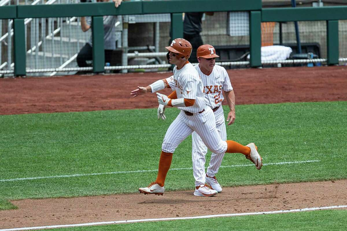 Texas outfielder Eric Kennedy (30) gets five from head coach David Pierce while running home from homering in the second inning against Tennessee during an NCAA college baseball game in the College World Series Tuesday, June 22, 2021, at TD Ameritrade Park in Omaha, Neb. (AP Photo/John Peterson)