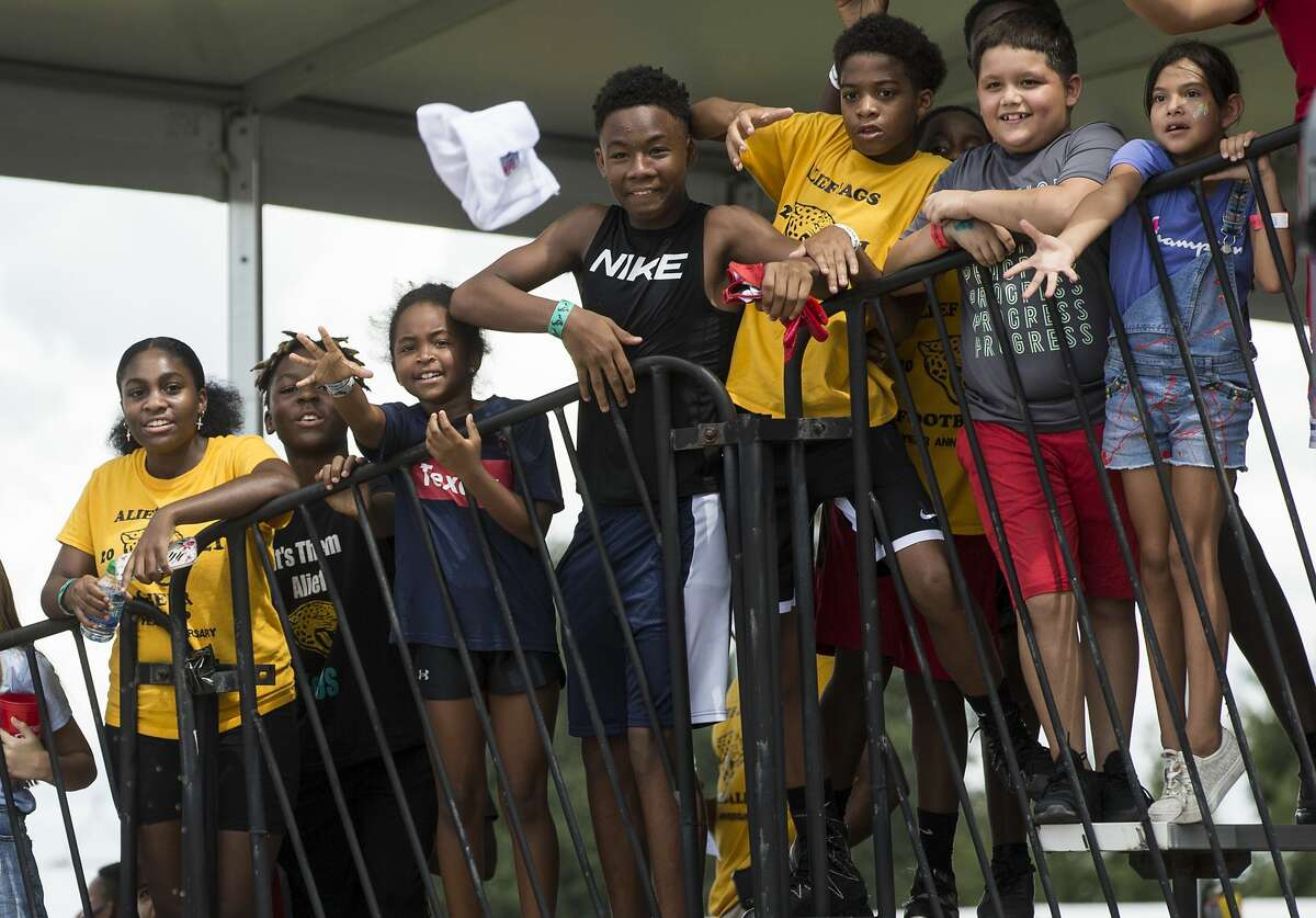 A group of youth football players from the FUN Football League wait for players to toss items up to their after an NFL training camp football practice Saturday, July 31, 2021, in Houston.