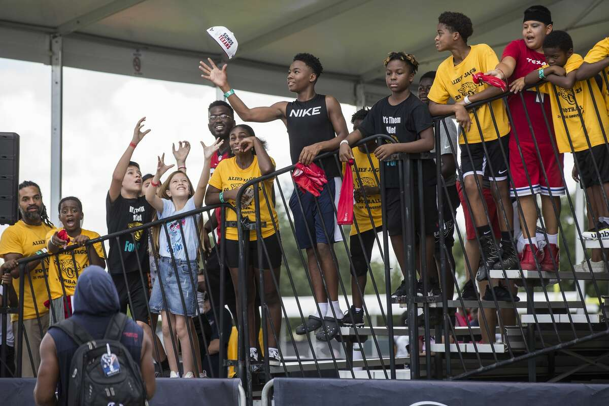 Houston Texans running back Mark Ingram tosses an autographed hat up to a group of youth football players from the FUN Football League after an NFL training camp football practice Saturday, July 31, 2021, in Houston.