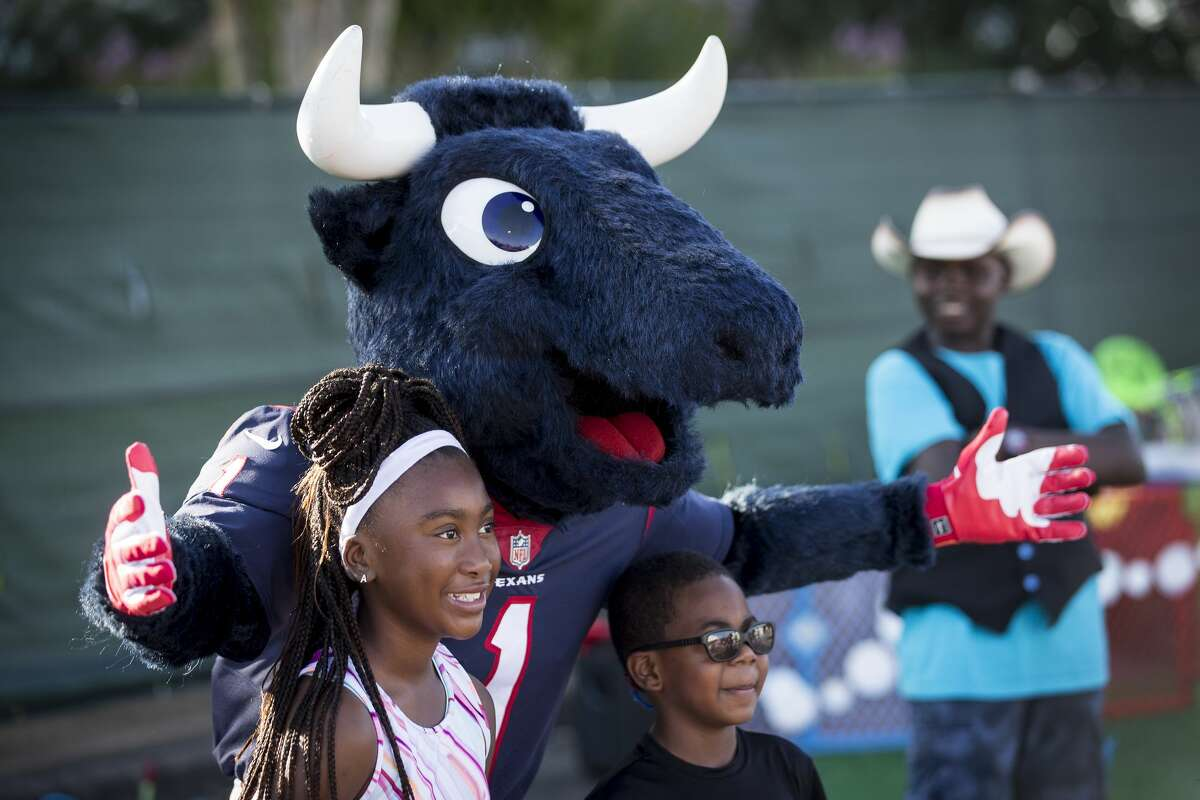 Texans mascot TORO, named the NFL's Mascot of the Year on Thursday, stops for a photo with Alayshia August and Karson August in the fan area at Texans NFL training camp football practice Saturday, July 31, 2021, in Houston.