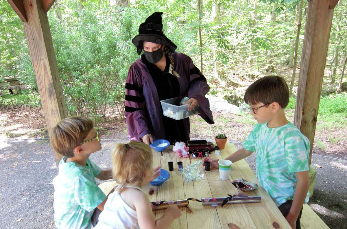 Professor Quickwit, played by Stamford Museum & Nature Center Director of Education Lisa Monachelli, hands out supplies during a potions class as part of a Wizard Picnic to celebrate Harry Potter's birthday on the grounds in Stamford, Conn., on Saturday July 31, 2021. Kids came dressed as wizards and took part in several activities like making their own wands, a potions class, a visit with some magical creatures from the nature center and snacks.