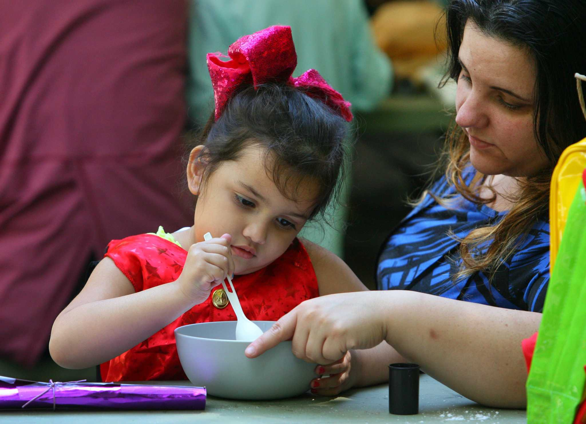 Samantha Ponce, 3, stirs ingredients in potion class as her mom Stefanie helps her hold the bowl during a a Wizard Picnic held to celebrate Harry Potter's birthday at Stamford Museum & Nature Center in Stamford, Conn., on Saturday July 31, 2021. Kids came dressed as wizards and took part in several activities like making their own wands, a potions class, a visit with some magical creatures from the nature center and snacks.