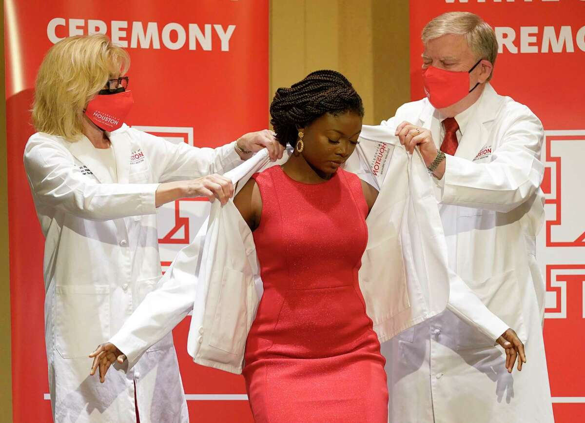 Dr. Ruth Bush, left, and Dr. Stephen Spann, put a white coat onto medical student Adebosola Karunwi, center, during the University of Houston College of Medicine ceremony held at the Hilton UH Saturday, July 31, 2021 in Houston.