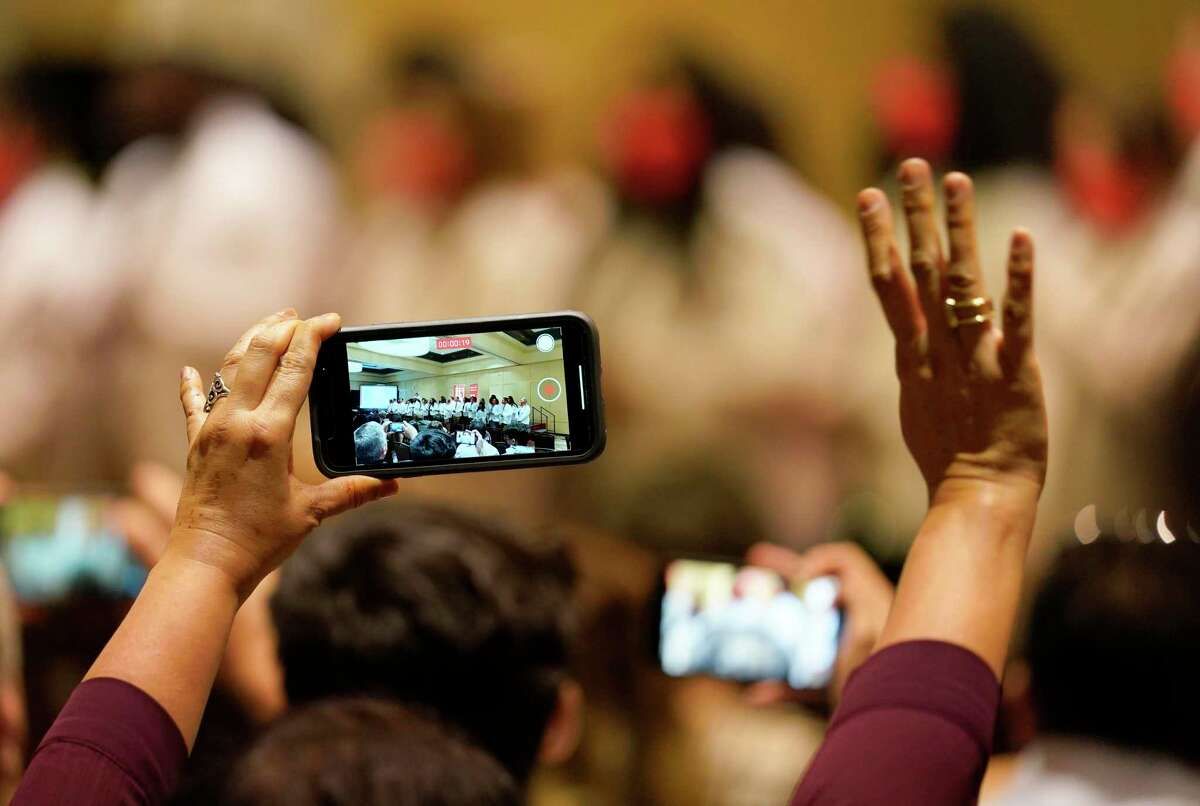 A woman video records and waves as the University of Houston medical students recite their student oath during the White Coat Ceremony held at the Hilton UH Saturday, July 31, 2021 in Houston.