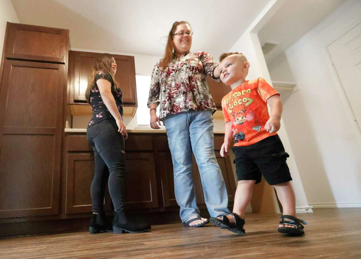 Brenda Price, center, tours her new home from Habitat For Humanity with her son, Samuel, and daughter, Daisy, Saturday in Conroe. Price is the first participant in the Family Promise program to receive a home from Habitat.