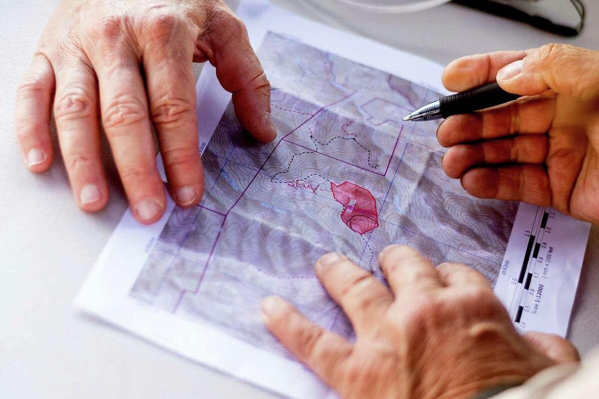 Volunteers examine a map of Pleasanton Ridge Regional Park while searching for missing runner Philip Kreycik.