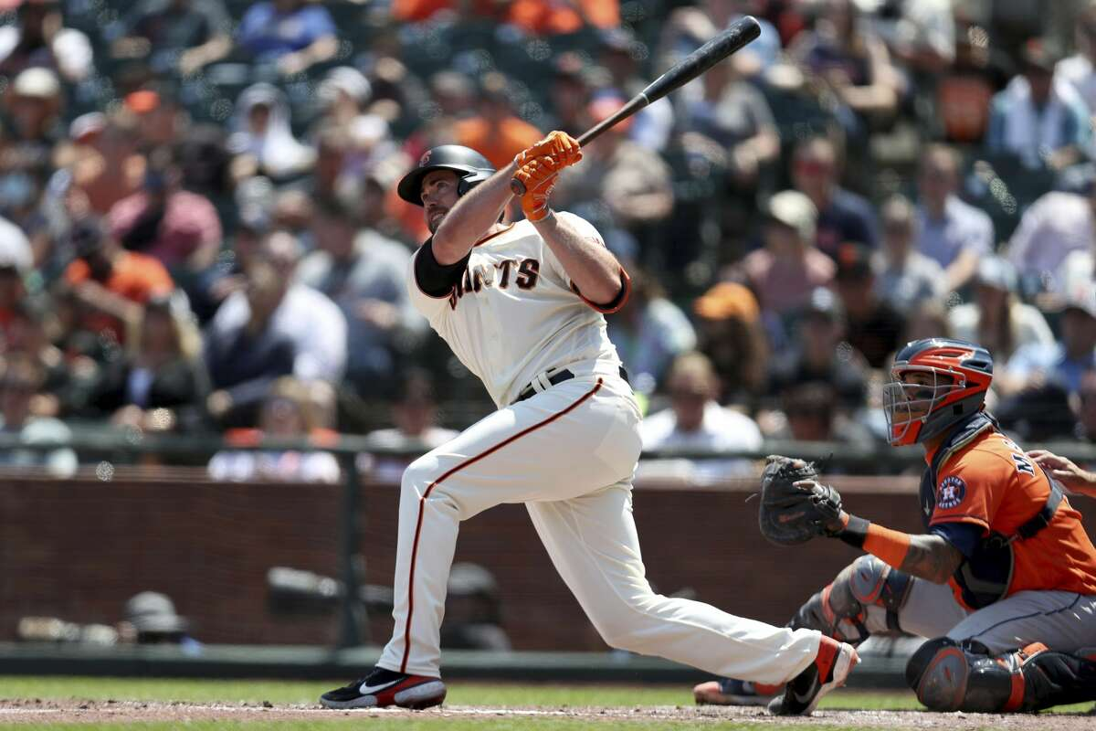 San Francisco Giants' Darin Ruf, left, hits a home run in front of Houston Astros' Martin Maldonado during the fifth inning of a baseball game in San Francisco, Saturday, July 31, 2021. (AP Photo/Jed Jacobsohn)