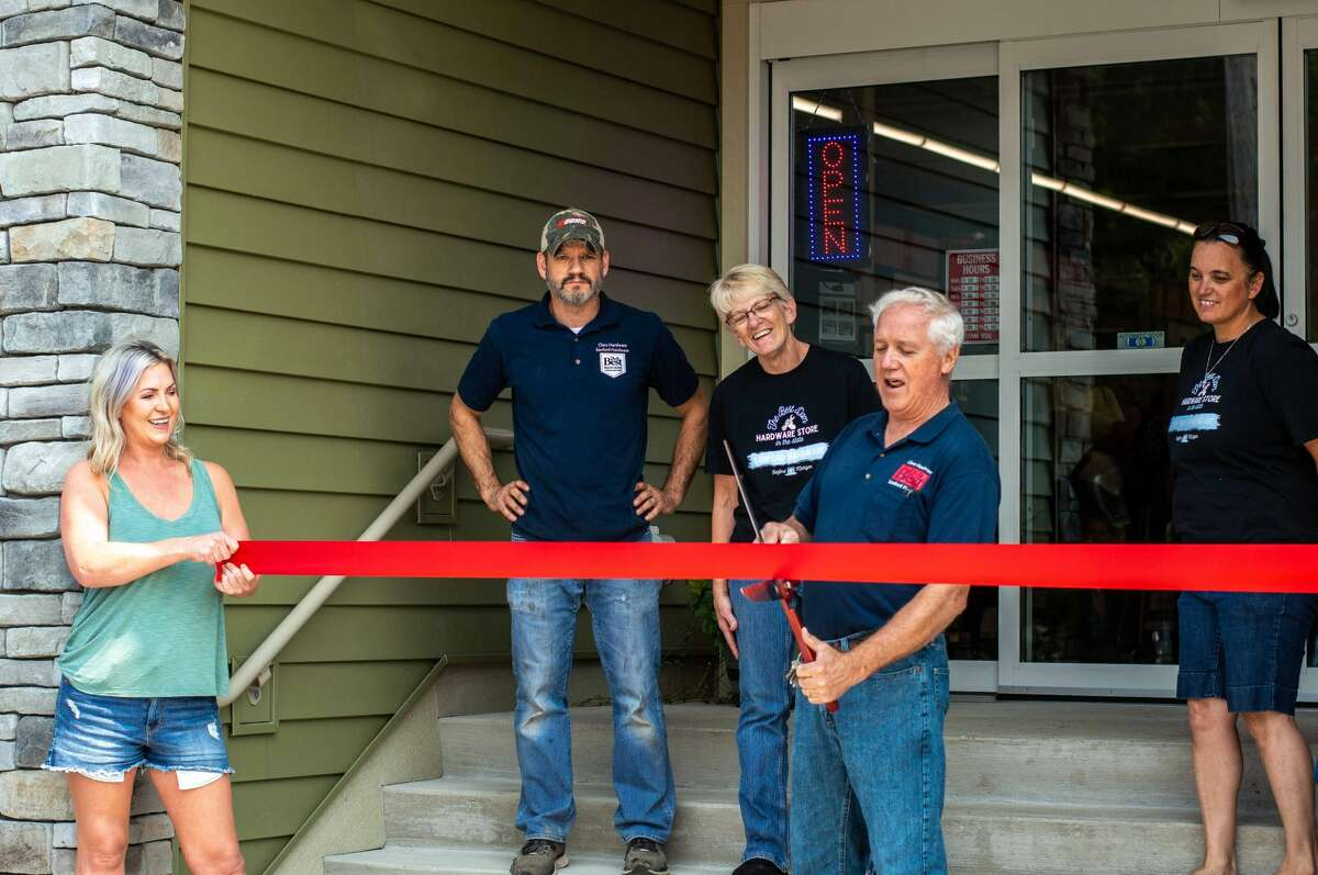 Sanford Hardware co-owner Denny Sian cuts a ribbon in front of his new store building on July 31, 2021 346 W. Saginaw Road. This building replaced the old one damaged from the 2020 Edenville Dam flood.