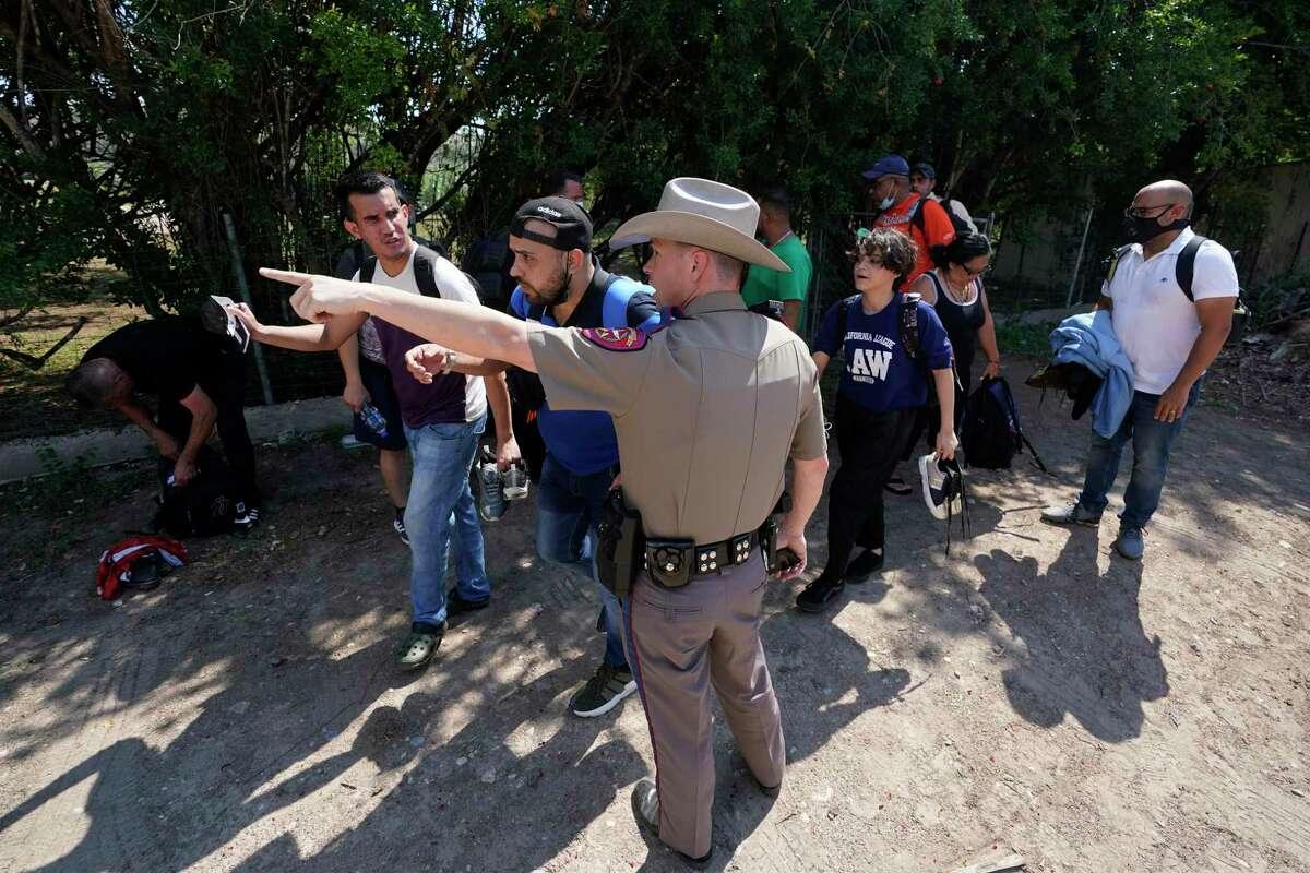 En esta fotografía de archivo del miércoles 16 de junio de 2021, un agente del Departamento de Seguridad Pública en Del Rio, Texas, dirige hacia un lugar a un grupo de migrantes que cruzaron la frontera y se entregaron a las autoridades.