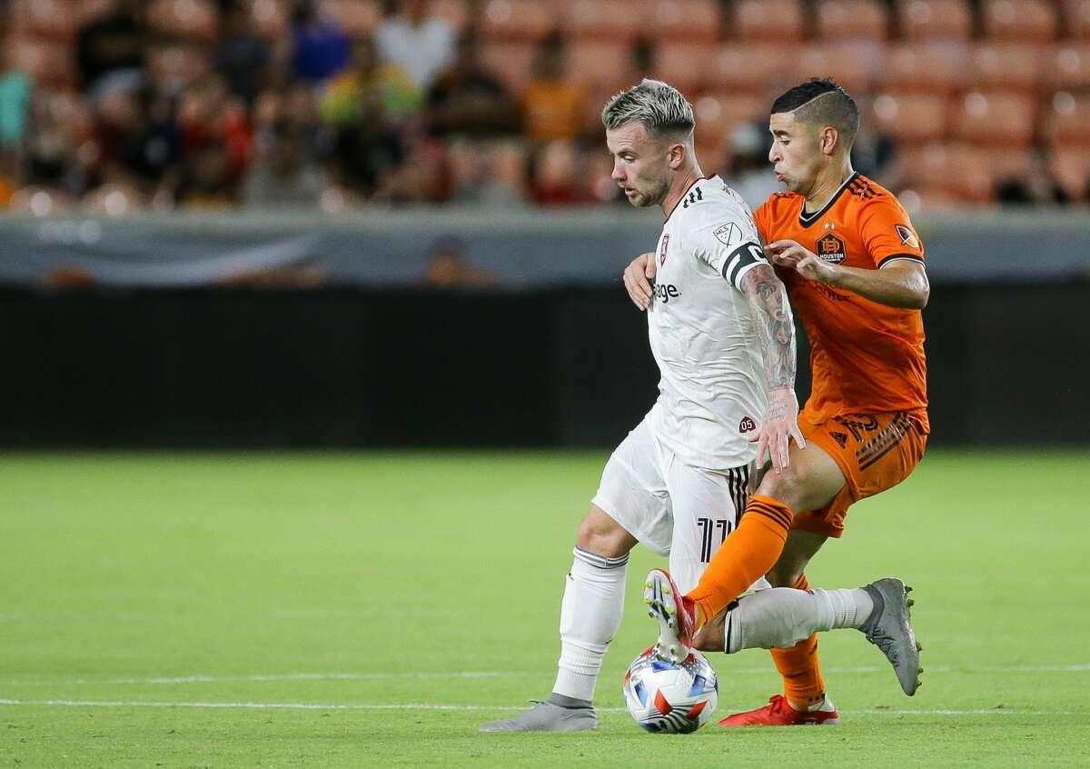 Real Salt Lake midfielder Albert Rusnak (11) is fouled by Houston Dynamo midfielder Matias Vera (22) during the second half of an MLS match at BBVA Stadium on Saturday, July 31, 2021, in Houston.