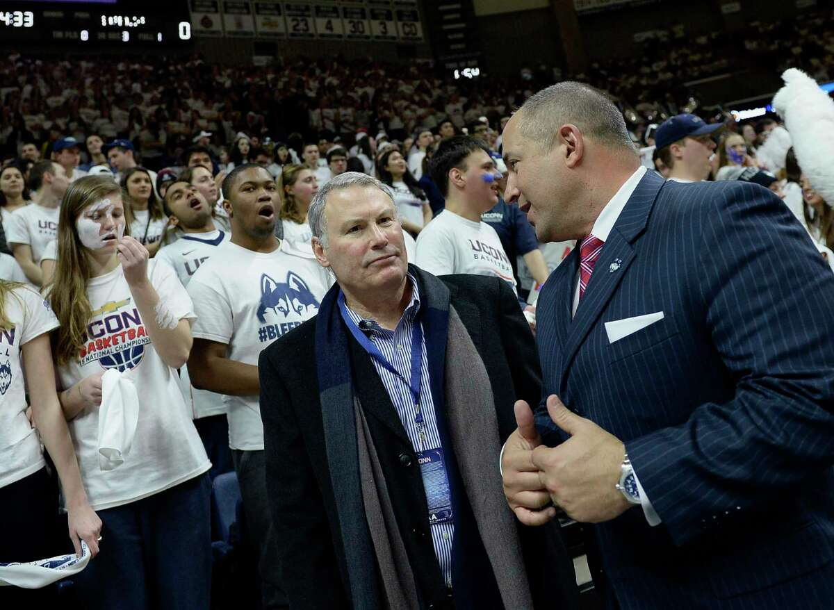 FILE - In this Feb. 13, 2017, file photo, American Athletic Conference commissioner Mike Aresco, center, talks with Connecticut athletic director David Benedict, right, before an NCAA college basketball game between UConn and South Carolina, in Storrs, Conn.Aresco says the league's new media rights deal with ESPN gives the AAC a platform similar to having its own branded network. The American and ESPN announced a 12-year agreement that runs through the 2031-32 school year. (AP Photo/Jessica Hill, File)