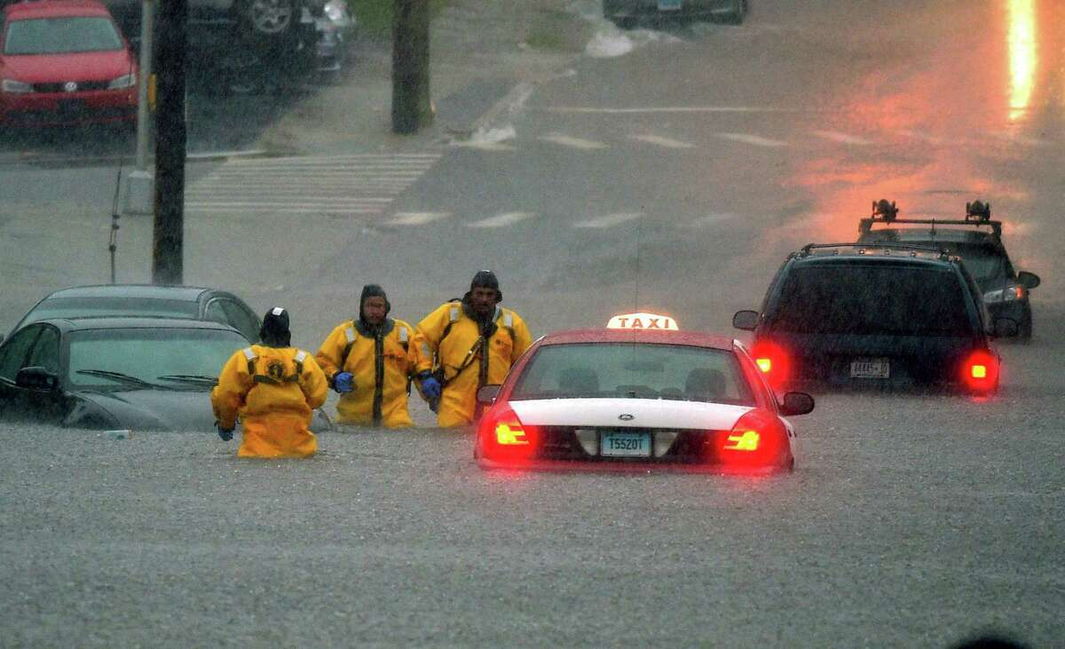 Firefighters head for higher ground after checking flooded cars for occupants on Broad Street after a line of thunderstorms dumped torrential rain across the region flooding roads in New London, Conn., Thursday Sept. 10, 2015.
