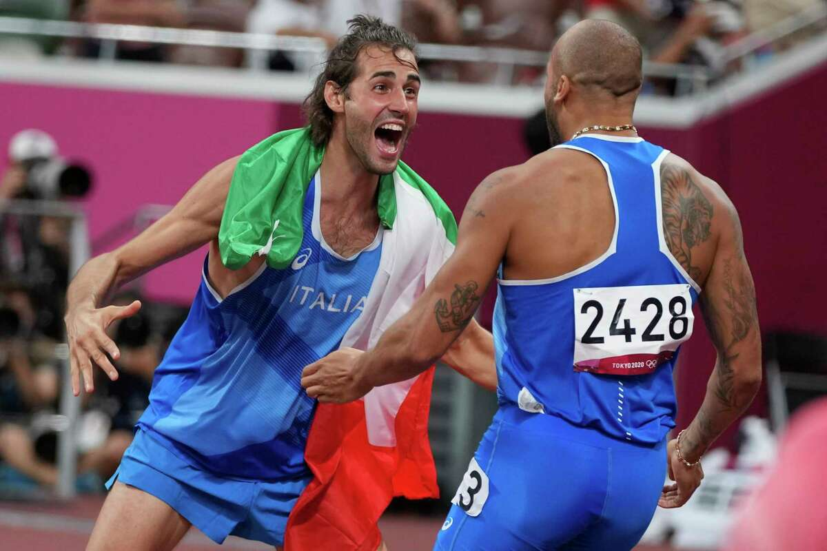 High jump gold medalist Gianmarco Tamberi, left, of Italy, congratulates compatriot Lamont Marcell Jacobs, after he won the final of the men's 100-meters at the 2020 Summer Olympics, Sunday, Aug. 1, 2021, in Tokyo.