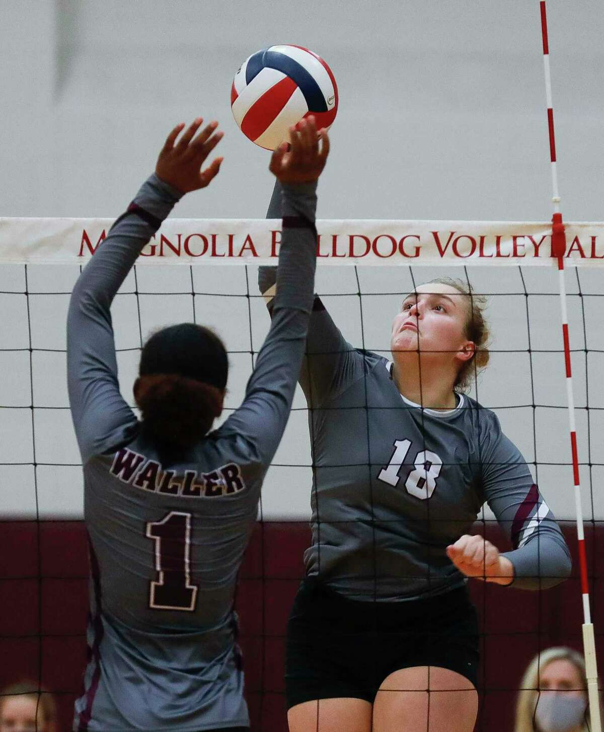 Magnolia middle blocker Brynn Botkin (18) get a shot past Waller right side hitter Essence Williams (1) during the first set of a District 19-5A high school volleyball match at Magnolia High School, Tuesday, Nov. 10, 2020, in Magnolia.
