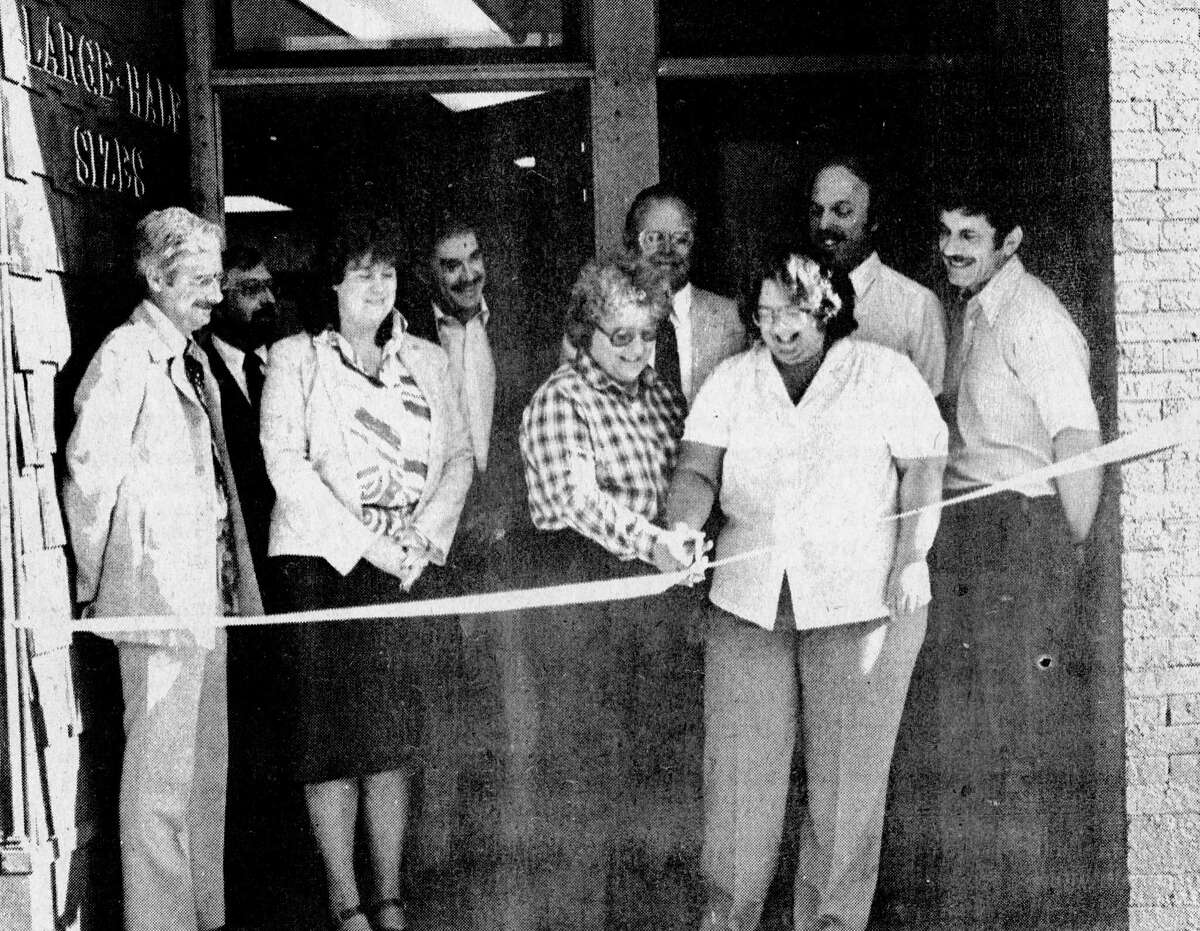 River Street's newest addition to the business community, Just For Her, opened its doors on July 30, 1981 at 410 River St. A crowd of well-wishers appeared for the opening ceremonies to watch owner Jerri Johnson (front center) and her daughter Justine Johnson (front right) cut the ribbon to open their store. (From left) Looking on were City Manager Bob Lewis, Ron Steinberg, Ginny Thomas, Dave Carlson, Mayor Vickers Hansen, Paul Burns and Paul Wilson. The photo was published in the News Advocate on July 31, 1981. (Manistee County Historical Museum photo)