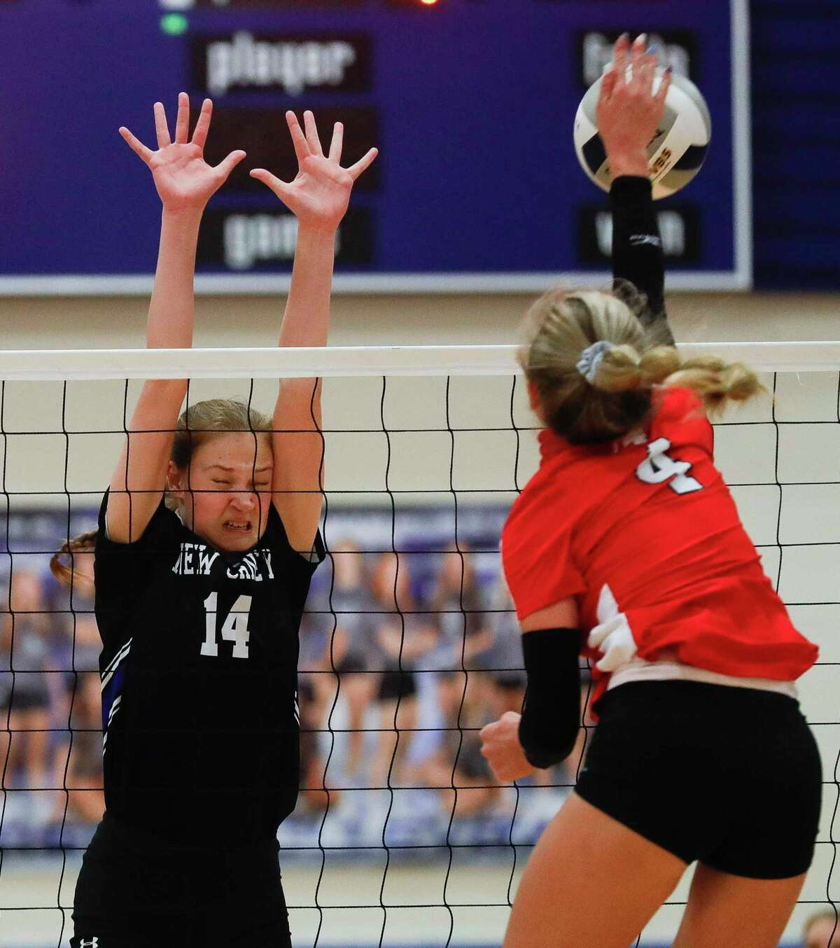 New Caney middle hitter Mia Chapa (14) pressures a shot by Porter setter Kyla Heine (4) during the first set of a district 20-5A high school volleyball match at New Caney High School, Tuesday, Nov. 3, 2020, in New Caney.