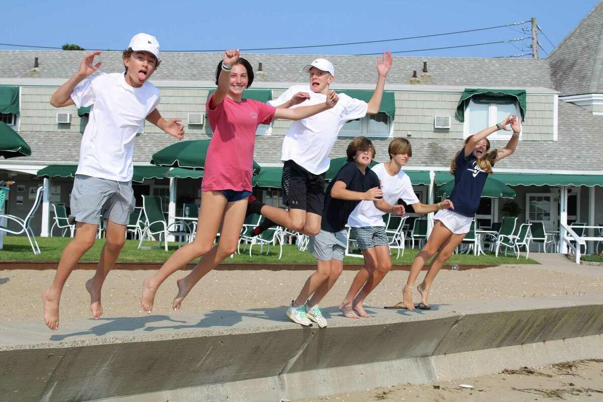 Follies cast members jump for joy on the beach.