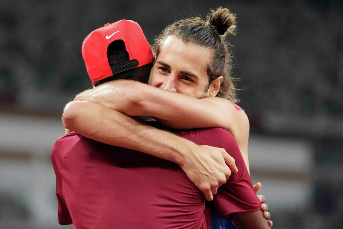 Gianmarco Tamberi, of Italy, embraces fellow gold medalist Mutaz Barshim, of Qatar, after the final of the men's high jump at the 2020 Summer Olympics, Sunday, Aug. 1, 2021, in Tokyo. (AP Photo/Matthias Schrader)