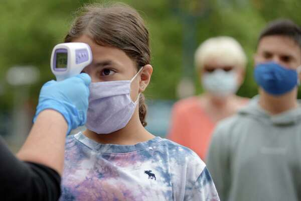 Maritime Aquarium Ocean Discovery Team summer campers including Julia Browning have their temperatures checked as they arrive at the aquairum Wednesday, July 15, 2020, in Norwalk, Conn.