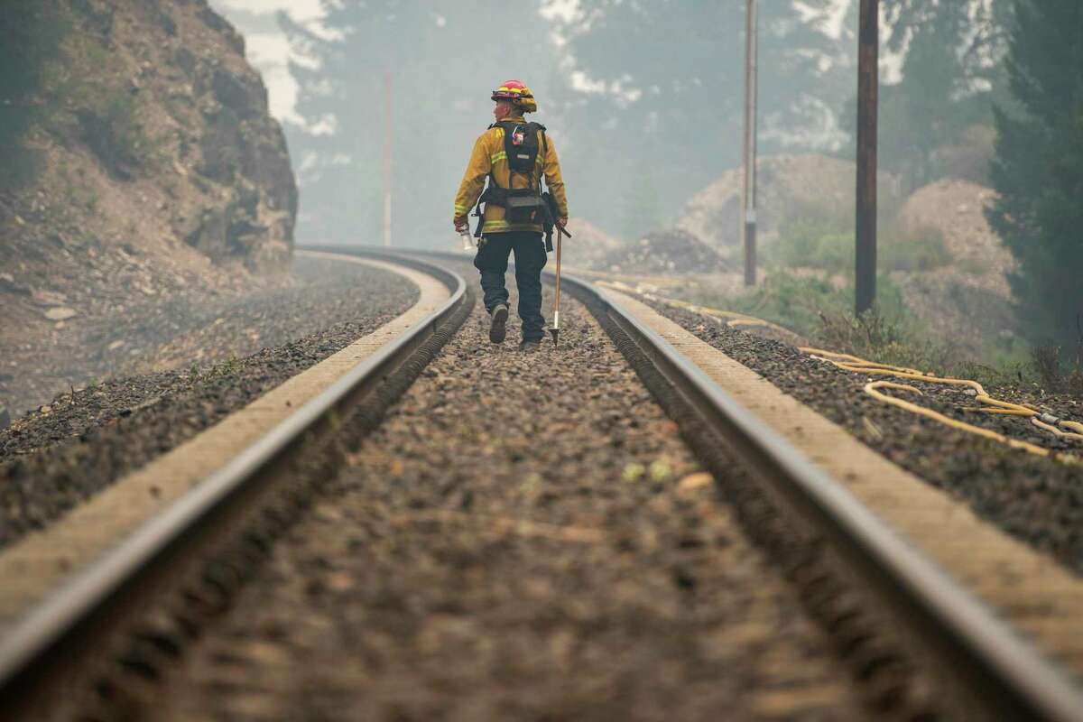 A firefighter looks for hot spots from the Dixie Fire near Quincy Junction, Calif., Friday, July 30, 2021. In what has grown into a grim ritual as wildfires plague Northern California, thousands have had to flee their homes. (Nic Coury/The New York Times)
