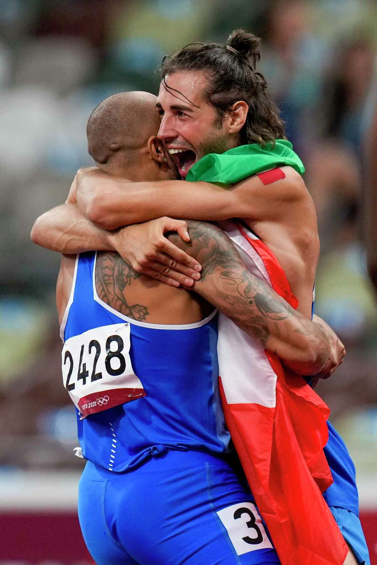 Lamont Jacobs, left, of Italy, celebrates after winning the men's the 100-meter final with high jump winner Gianmarco Tamberi, also of Italy, at the 2020 Summer Olympics, Sunday, Aug. 1, 2021, in Tokyo.