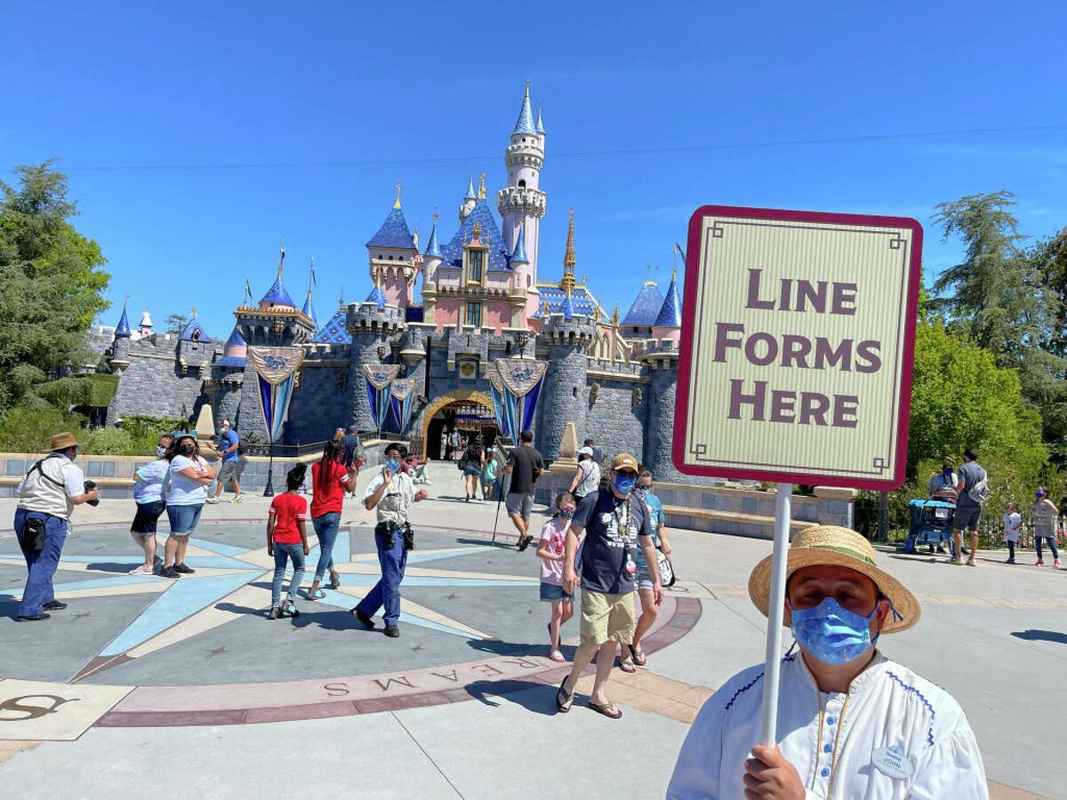 A Disneyland employee forms a line for visitors to take pictures in front of Sleeping Beauty Castle in Anaheim, CA, on Friday, April 30, 2021.